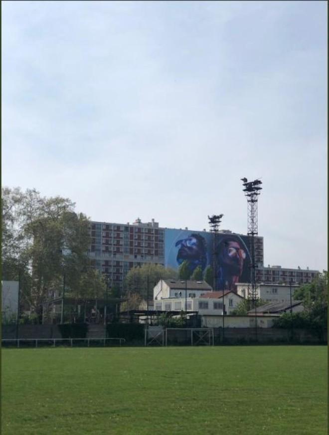 Un géant poster de ''Deux Frères'' de PNL accroché sur un immeuble dans la cité de leur enfance